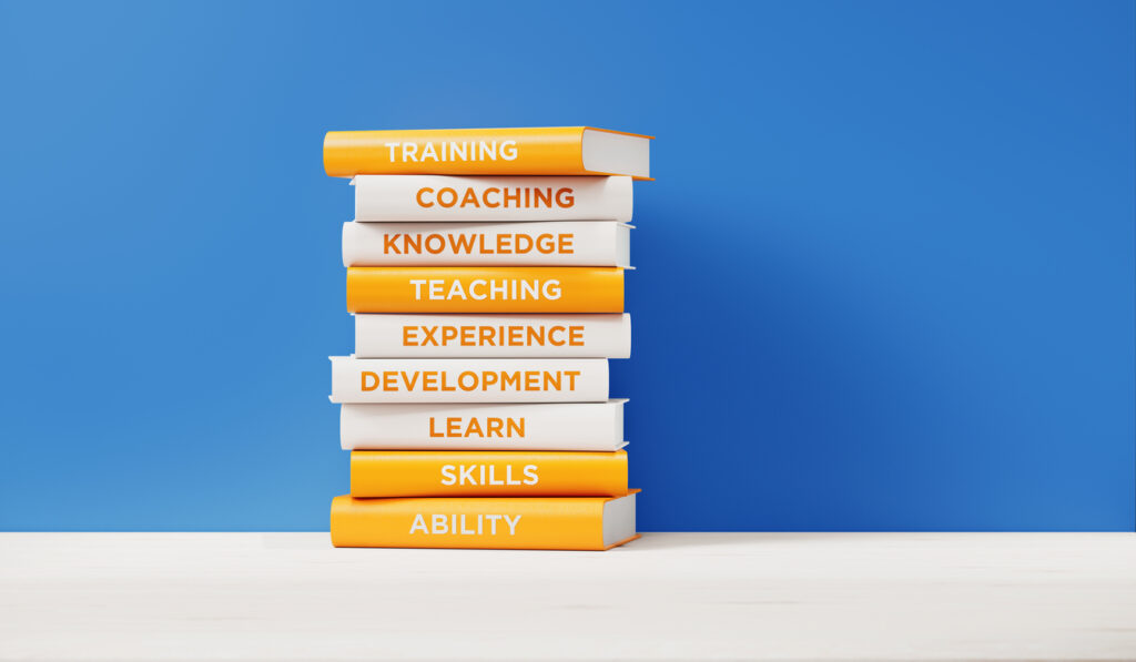Books of Training And Development in Front of Blue Wall