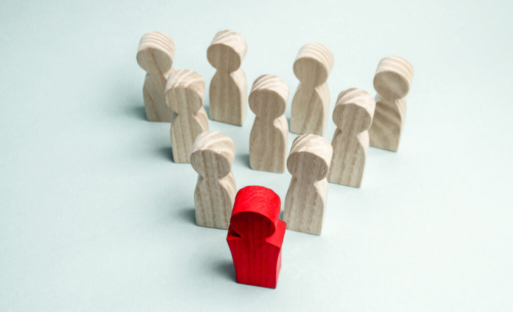 Wooden figures of people. The boss of the business team indicates the direction of movement to the goal. The crowd is following the leader. The concept of leadership and team management. Teamwork.